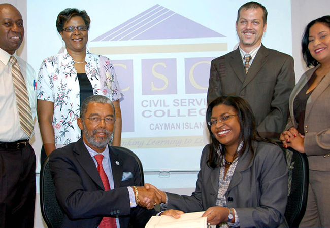 UCCI President Roy Bodden and Chief Officer of the Portfolio of Civil Service Gloria McField-Nixon launch the Civil Service College's first joint degree offering. Also seen are (standing from L) UCCI Department Chair Dr. Allan Young, UCCI Deputy Registrar Diane Campbell, CSC Manager of Leadership Learning David Stock and CSC Deputy Director Andrea Fa'amoe.