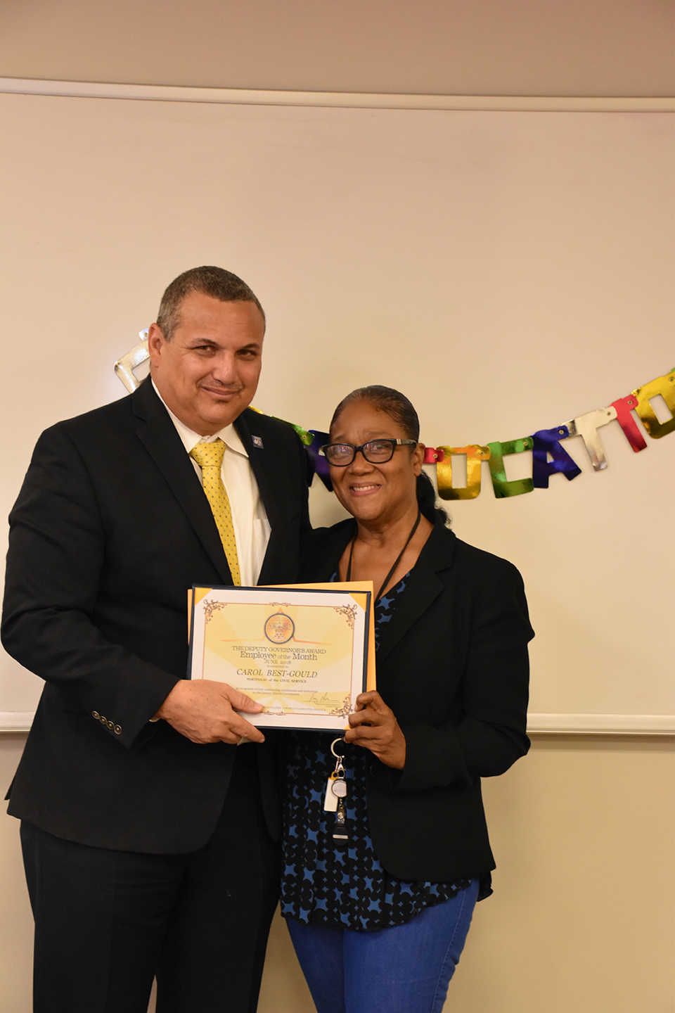 Deputy Governor Franz Manderson presents Employee of the Month certificate to Carol Best Gould.